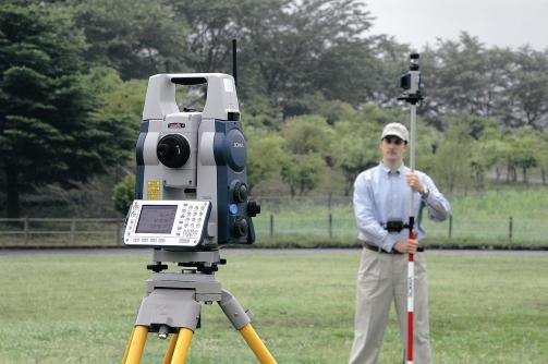 A total station and a person holding a total pole.
